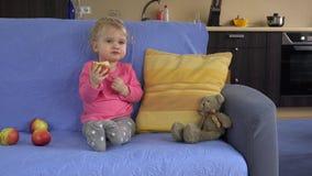 Schitterende het kindzitting van het peuterjonge geitje op de bank en het eten van groot appelfruit stock videobeelden