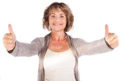 Schitterende hogere dame die duim-omhoog toont stock foto