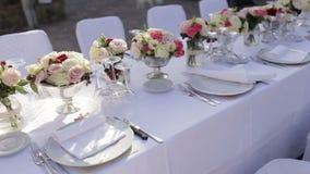 Schitterende huwelijkslijst die voor boete plaatsen die in openlucht dineren stock footage
