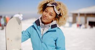 Schitterende in jonge vrouw met haar snowboard stock videobeelden