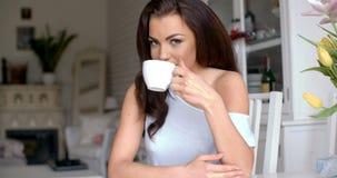 Schitterende jonge vrouwenzitting het drinken koffie stock footage
