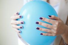 Schitterende manicure, donker purper teder kleurennagellak, close-upfoto Het wijfje overhandigt eenvoudige achtergrond Stock Afbeelding