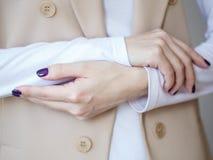 Schitterende manicure, donker purper teder kleurennagellak, close-upfoto Het wijfje overhandigt eenvoudige achtergrond van vrijet Stock Afbeeldingen