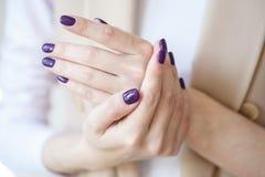 Schitterende manicure, donker purper teder kleurennagellak, close-upfoto Het wijfje overhandigt eenvoudige achtergrond van vrijet Royalty-vrije Stock Foto
