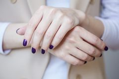 Schitterende manicure, donker purper teder kleurennagellak, close-upfoto Het wijfje overhandigt eenvoudige achtergrond van vrijet Royalty-vrije Stock Afbeelding