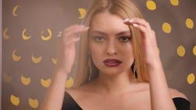 Schitterende mannequin met het mooie haar stellen, langzame motie, gele bokehachtergrond stock videobeelden