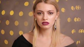 Schitterende mannequin met het mooie haar stellen, langzame motie, gele bokehachtergrond stock video