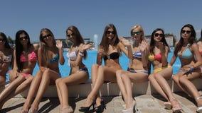 Schitterende meisjes die dichtbij de pool en het lachen zitten stock video