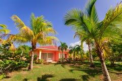 Schitterende mening van het huis van de toevluchtbungalow status in tropische tuin tegen blauwe hemelachtergrond Royalty-vrije Stock Afbeeldingen