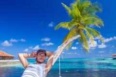 Schitterende Mens die op Strandpalm rusten Royalty-vrije Stock Afbeeldingen