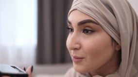 Schitterende moslimvrouw die make-up professioneel doen Borstelwimpers met mascara Het dragen van beige headscarf Witte muur  stock video