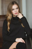 Schitterende nadenkende vrouw in zwarte kledingszitting op leerbank Stock Foto's