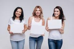 Schitterende positieve dames die de tekens houden Stock Foto's