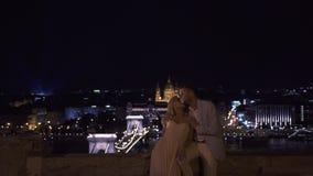 Schitterende sensuele jonggehuwden die en op de stadsbrug bij nacht kussen omhelzen De zitting van het nachthuwelijk stock footage