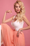 Schitterende sexy vrouw met blond krullend haar in elegante kledingsposin Stock Foto