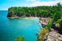 Schitterende verbazende natuurlijke rotsachtige strandmening en rustig azuurblauw duidelijk water royalty-vrije stock afbeeldingen