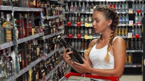 Schitterende vrouw die aan de camera glimlachen terwijl het winkelen voor wijn stock footage