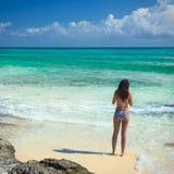 Schitterende vrouw die in bikini op overzees tropisch strand bekijken Locat Stock Foto