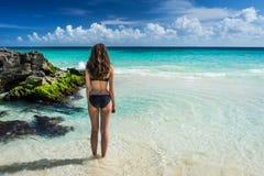 Schitterende vrouw die in bikini op overzees tropisch strand bekijken Locat Stock Fotografie