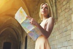 Schitterende vrouw die een kaart houden terwijl in het buitenland het reizen stock afbeelding