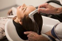 Schitterende vrouw die haar die haar hebben door kapper wordt gewassen stock afbeeldingen