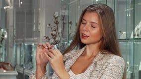 Schitterende vrouw die op dure ringen bij de juwelenopslag proberen stock footage
