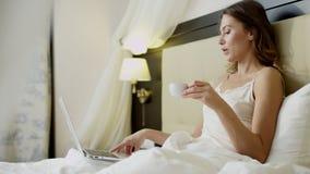 Schitterende vrouw die videovertaling op haar laptop doen terwijl het drinken van koffie in bed stock footage
