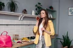 Schitterende vrouw in geel jasje en roze zak met mobiel in de keuken royalty-vrije stock fotografie