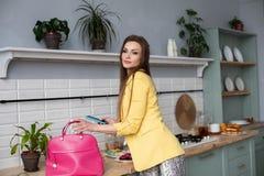 Schitterende vrouw in geel jasje en roze zak met mobiel in de keuken stock afbeelding