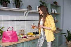 Schitterende vrouw in geel jasje en roze zak met mobiel in de keuken stock fotografie