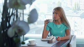 Schitterende vrouw het drinken thee, die op iemand bij het restaurant voor ontbijt wachten stock footage