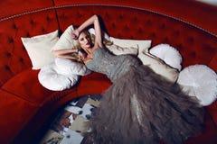Schitterende vrouw met blond haar in elegante kleding die op rode divan liggen Stock Afbeeldingen