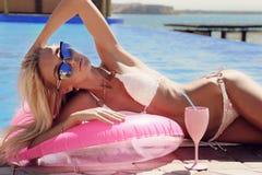 Schitterende vrouw met blond haar in het elegante zwempak stellen naast zwembad Royalty-vrije Stock Afbeeldingen