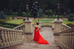 Schitterende vrouw in rode kleding met zwarte ballons Royalty-vrije Stock Afbeelding