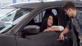 Schitterende vrouwenzitting in een nieuwe auto bij handel drijven, die aan haar vriend het spreken stock videobeelden