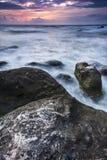 Schitterende zonsondergang met rotsen in golven Royalty-vrije Stock Fotografie