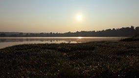 Schitterende Zonsondergang op een Meerbank met een Oranje Zon, een Vlot Urface en een Groen , stock footage