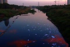Schiuma dagli agenti schiumogeni (detersivo di schiumatura) sul fiume fotografie stock