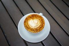 Schiuma del latte del caffè con forma del cuore immagini stock