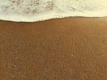 Schiuma dell'onda e spiaggia giallo sabbia, alta marea, mare caldo e spiaggia di sabbia Fotografie Stock Libere da Diritti