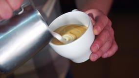 Schiuma di versamento del latte di barista professionale sopra caffè nella tazza bianca che crea cappuccino perfetto archivi video