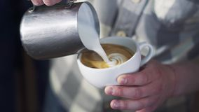 Schiuma di versamento del latte di barista sopra caffè che produce un cappuccino perfetto e che crea un cuore bianco archivi video