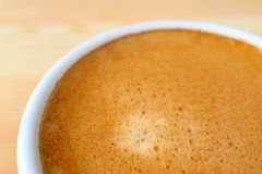 Schiuma italiana aromatica alta chiusa del caffè del caffè espresso in tazza di caffè macchiato, con il fuoco selettivo Fotografia Stock