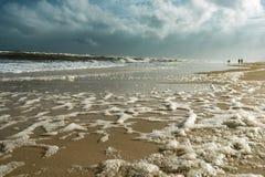 Schiuma Seaspray della spiaggia di alta marea con la gente fotografia stock