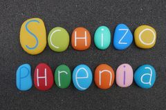 Schizophrenia text composed with multi colored sea stones over black volcanic sand. Word Schizophrenia composed with colored and carved sea stones over black stock photography