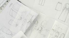 Schizzi dei vestiti, fogli di carta bianchi attinti video d archivio