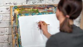 Schizzo del disegno della donna del pittore su tela facendo uso della vista posteriore del primo piano grigio della matita stock footage
