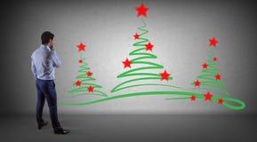 Schizzo di sorveglianza degli alberi di Natale dell'uomo d'affari su un renderi della parete 3D Fotografia Stock