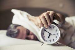 Schläfrige Bedeckungsohren des jungen Mannes mit Kissen, wie er Wecker betrachtet Stockbild