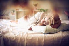 Schläfrige blonde Frau im Bett Lizenzfreie Stockfotos